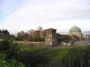 An image taken from slightly above looking down on a collection of classical inspired buildings including one with a dome.  Buildings are surrounded by paved pathways and green grassy areas.